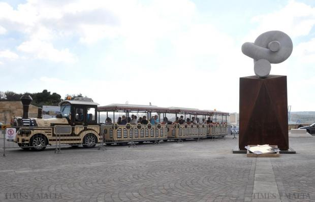 A train carrying tourists drives past the new but controversial monument in Castille Square on November 9. The sculpture is said to symbolize Malta's geographic reality of a chain between two continents. It also symbolises the unity between the EU and Africa. Photo: Chris Sant Fournier