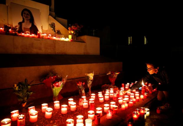 An activist places candles on the Great Siege monument, after rebuilding a makeshift memorial to assassinated anti-corruption journalist Daphne Caruana Galizia, during a vigil to mark thirteen months since her murder, in Valletta. Photo: Reuters