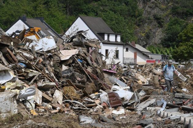 Merkel demands faster climate action as flood deaths rise