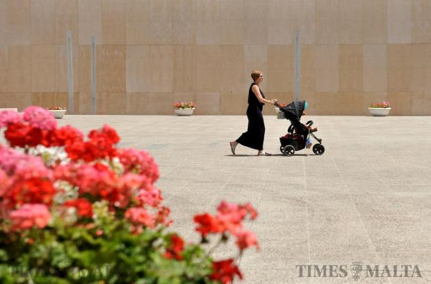 A woman pushes a child in a pushchair at The Point in Sliema on June 6. Photo: Chris Sant Fournier