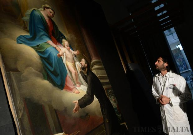 Pierre Bugeja from Prevarti studios describes the restoration process after the completion of Ħamrun's titular painting of St Cajetan, on April 13. Photo: Matthew Mirabelli
