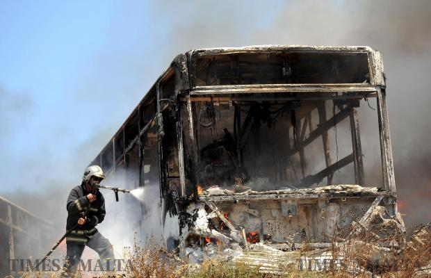 A fireman tries to extinguish the flames which moments earlier engulfed a bus in a vehicle storage facility in San Gwann on June 21. Photo: Chris Sant Fournier