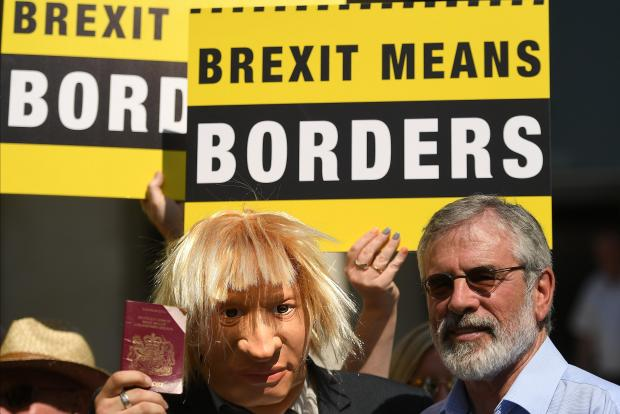An actor wearing a Boris Johnson mask is joined by Sinn Fein's Gerry Adams during a 'Borders Against Brexit' protest in the border town of Dundalk.