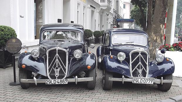 Two dark blue Citroen Traction models at the Hanoi Hotel Metropole.
