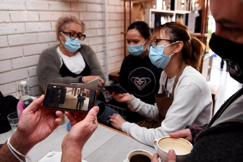 Staff and customers watch a press conference by acting Victorian Premier James Merlino on a phone at a cafe in Melbourne.
