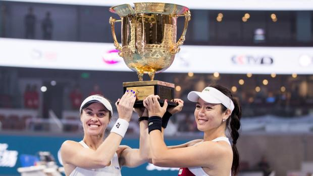 Martina Hingis of Switzerland (L) and Chan Yung-Jan of Taiwan celebrate with the trophy after winning the match.