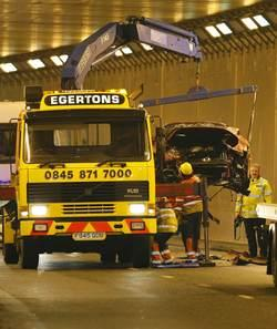 Recovery workers remove the car of Manchester United's Portuguese soccer player Cristiano Ronaldo after it crashed in a tunnel near Manchester Airport in northern England.