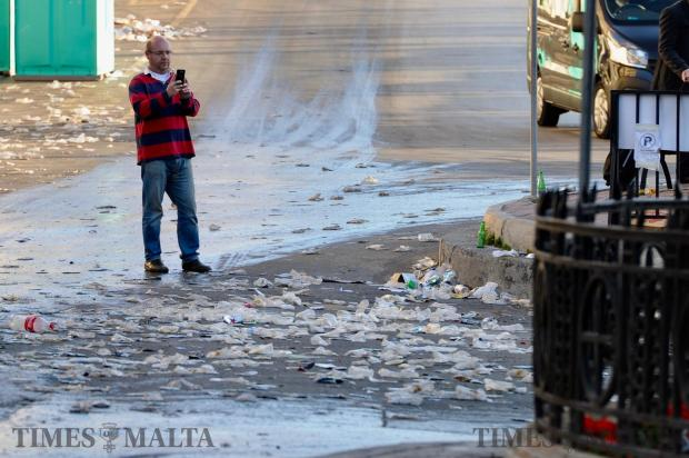 A man takes a photograph of the mess left at Spinola Bay the morning after St Patrick's Day celebrations on March 18. Photo: Steve Zammit Lupi