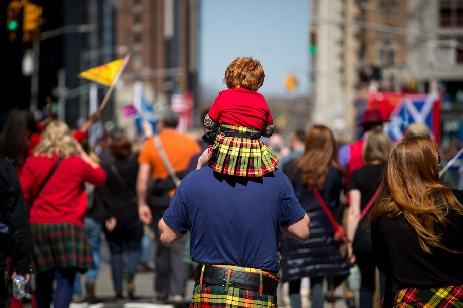 A toddler wearing a kilt gets a piggyback ride during the annual Tartan Day Parade in New York, the United States, on April 6, 2019. Photo: Xinhua