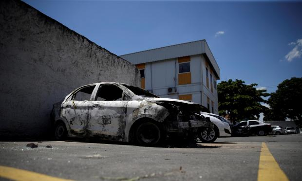 A burnt car in which a body was found during searches for the Greek ambassador.