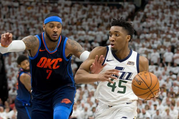 Utah Jazz guard Donovan Mitchell (45) dribbles the ball as Oklahoma City Thunder forward Carmelo Anthony (7) defends during the second half of game four of the first round of the 2018 NBA Playoffs at Vivint Smart Home Arena. Mandatory Credit: Russ Isabella-USA TODAY Sports