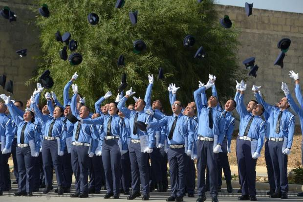 New police recruits throw their caps into the air after their passing-out parade at the Police Academy in Ta' Kandja on October 21. Photo: Matthew Mirabelli