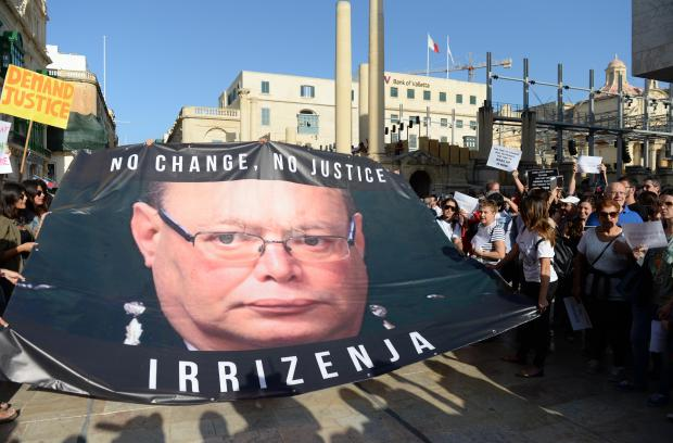 Students carry a banner with the face of Malta's Police Commissioner demanding his resignation outside the Parliament Building in Valletta, on October 22. Thousands gathered for a national rally in the capital after blogger Daphne Caruana Galzia was murdered outside her home after a car bomb went off. Photo: Matthew Mirabelli