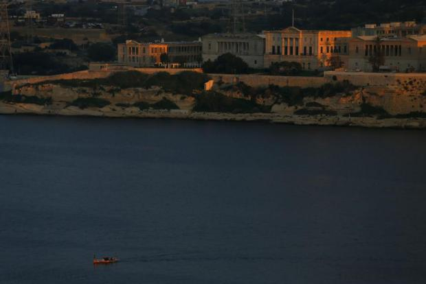 A traditional water taxi makes its way across Grand Harbour, overlooked by Bighi Hospital in Kalkara, on November 19. Photo: Darrin Zammit Lupi
