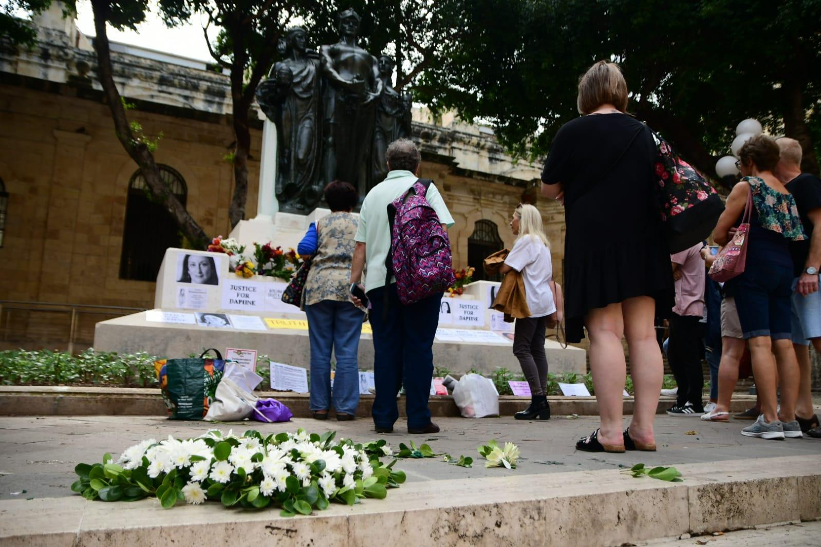 People pay their respects, as a wreath placed by a PN delegation lies on the ground. Photo: Jonathan Borg