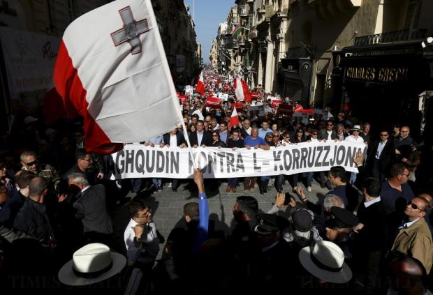 "Protestors walk behind a banner reading ""United against corruption"" during a demonstration against alleged government corruption in Valletta on March 6. Photo: Darrin Zammit Lupi"
