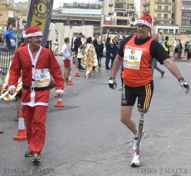 Raniero Borg and his brother-in-law amputee Noel Cacciottolo walk the last few hundred meters towards the finish line of the 2015 Mdina 2 Spinola Christmas Road Race in St Julian's on December 20. Photo: Mark Zammit Cordina