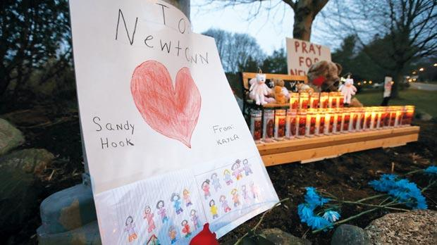 A sign stands at a makeshift memorial in Newtown, Connecticut early yesterday. Twelve girls, eight boys and six adult women were killed in the shooting on Friday at the Sandy Hook Elementary School in Newtown. Photo: Reuters