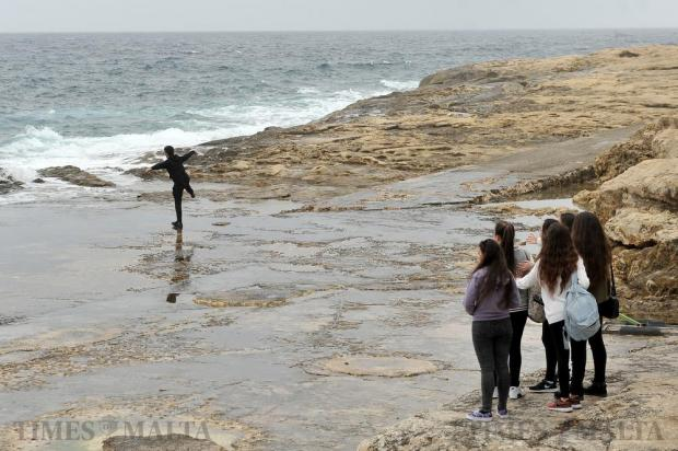 A teenage boy shows off in front of a group of teenage girls at Qui-si-sana in Sliema on February 17. Photo: Chris Sant Fournier