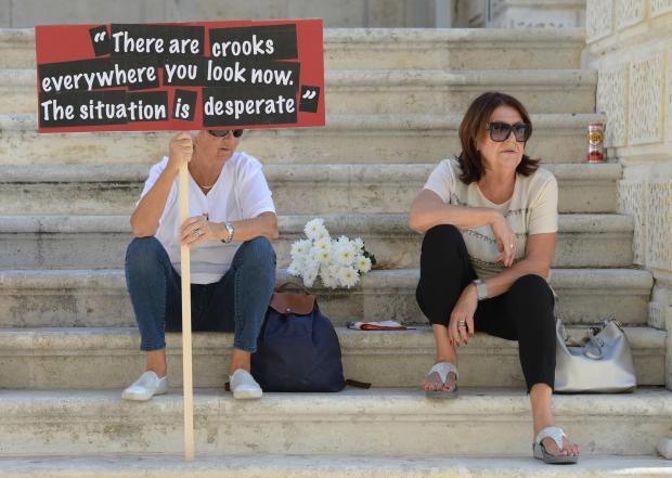 A lady carries a banner with a quote from Daphne Caruana Galzia's blog during a national rally in Valletta, on October 22. Thousands gathered in protest after the blogger was murdered outside her home after a car bomb went off on October 16. Photo: Matthew Mirabelli