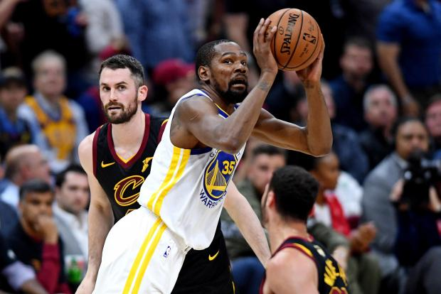 Golden State Warriors player Kevin Durant (centre) eyes the basket against Cleveland Cavaliers.