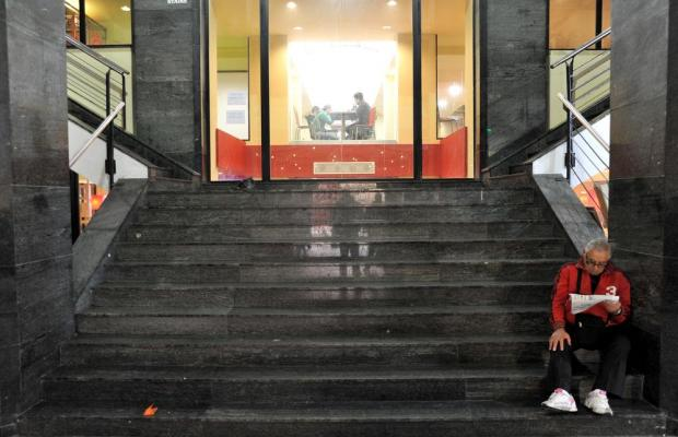 A man reads a newspaper on the steps of the City Gate shopping centre on December 19. Photo: Chris Sant Fournier