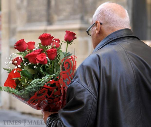 A man carries a bouquet of roses on the eve of Valentine's Day in Valletta on February 13. Photo: Chris Sant Fournier
