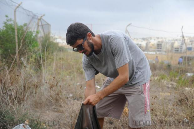 A volunteer collects litter outside the MIDI gate on Manoel Island in a failed attempt to gain access to clean up the area on September 17. Photo: Steve Zammit Lupi