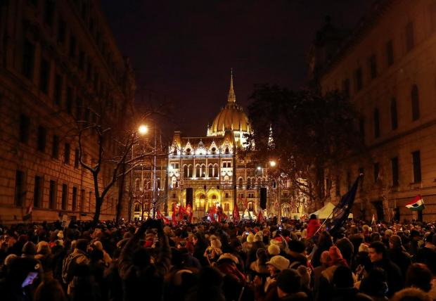 "People take part in a protest against a proposed new labor law, billed as the ""slave law"", in front of the parliament building in Budapest. Photo: Reuters"