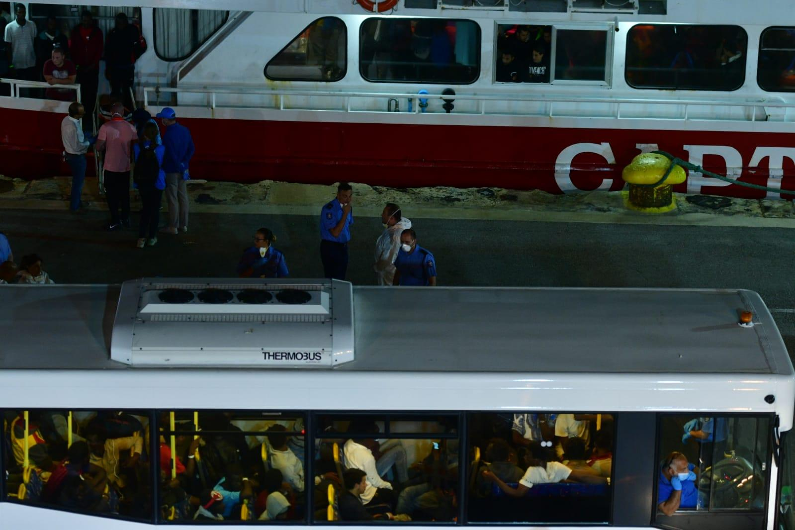 The migrants being put on buses for transport to Hal Far detention centre.