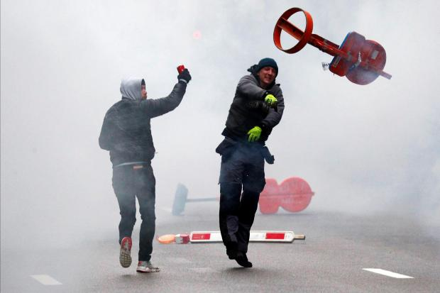 A far-right supporter throws a traffic sign during the protest. Photo: Reuters