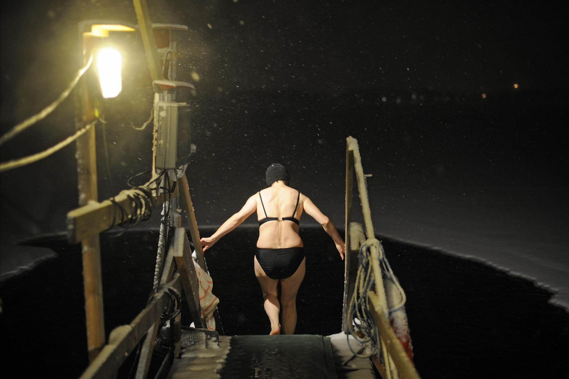 File: A woman prepares to get in the frozen river in Rovaniemi on December 18, 2008. The sauna tradition in Finland has been inscribed on the UNESCO Lists of Intangible Cultural Heritage on December 17, 2020.