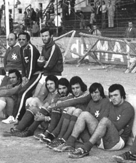 Coach Terenzio Polverini (second left, wearing dark sunglasses) following the national team from the sidelines during an international match at the old Gzira stadium.