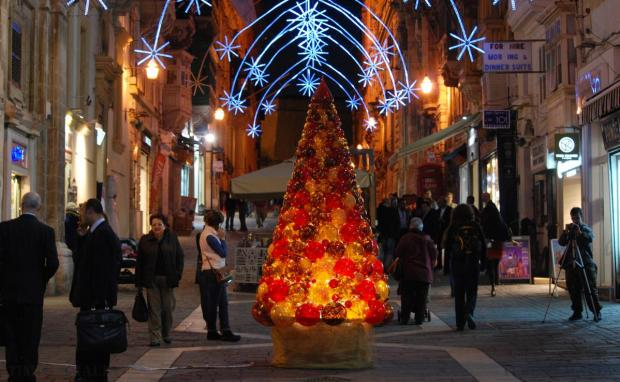 Shoppers walk past a Christmas tree made of glass baubles in Valletta's Merchant's Street on 19 December. Photo: Mark Zammit Cordina