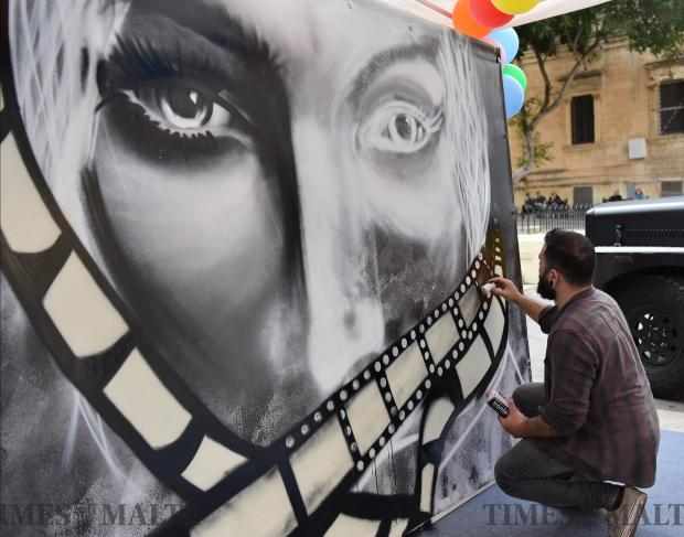 A graffiti artist spray paints the face of a woman in Valletta on November 11. Photo: Mark Zammit Cordina