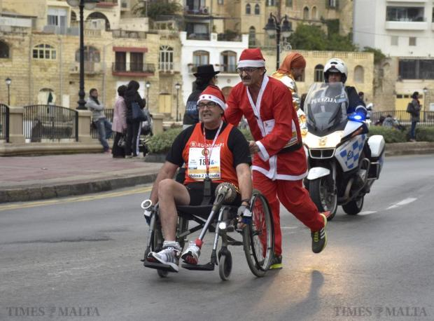 Raniero Borg pushes his brother-in-law amputee Noel Cacciottolo in a wheelchair towards the finish line of the 2015 Mdina 2 Spinola Christmas Road Race in St Julian's on December 20. Photo: Mark Zammit Cordina