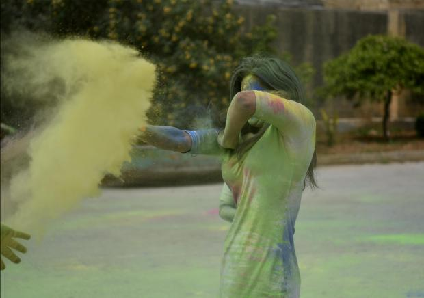 A woman covers her face from powder paint during the Holi Festival organized by the Indian Community held in St Venera on April 06. Photo: Mark Zammit Cordina