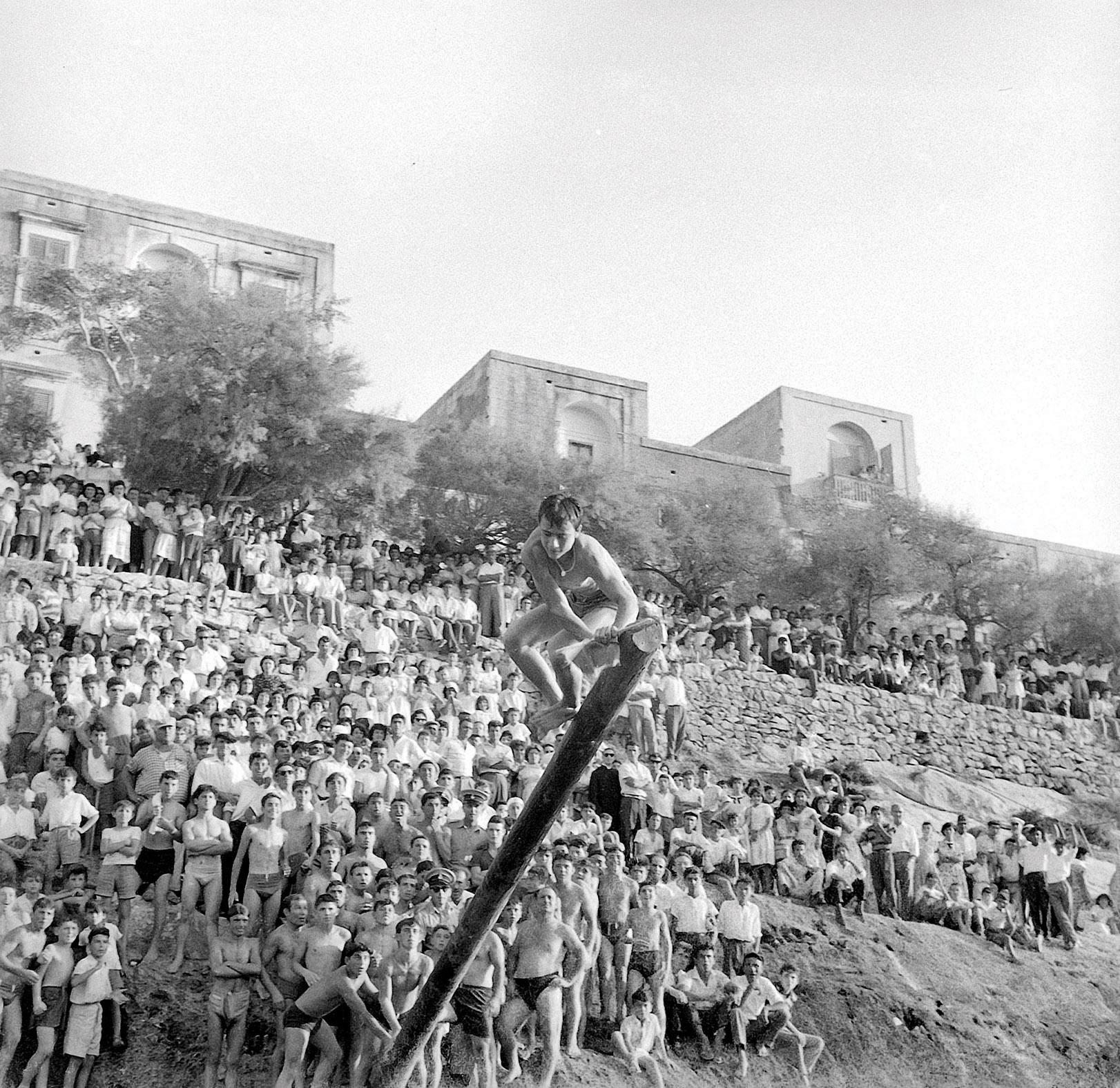 A young man trying his luck at a <em>ġostra </em>(greasy pole) organised during the feast of Our Lady of Mount Carmel in the 1950s. Photo: Kikku Cremona
