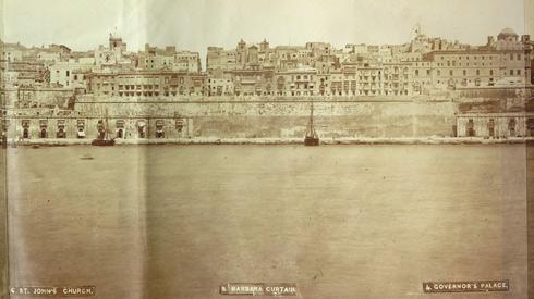 A 19th century photograph of Barriera Wharf with annotations at the bottom indicating Valletta landmark buildings.