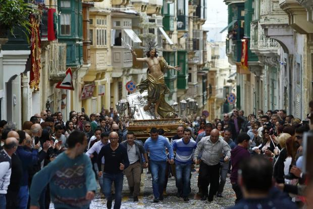 Statue bearers run while carrying a statue of the Risen Christ during an Easter Sunday procession in Cospicua on April 5. Photo: Darrin Zammit Lupi