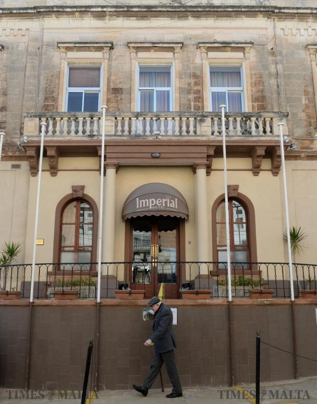 An elderly man walks past a Mepa permit to turn the Imperial Hotel in Sliema into an old people's home on January 13. Photo: Matthew Mirabelli