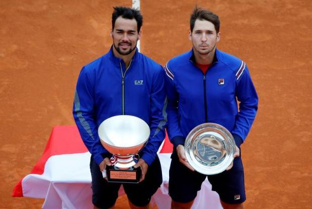 Italy's Fabio Fognini poses with Serbia's Dusan Lajovic as they pose with the winner and runner up trophies after the final.