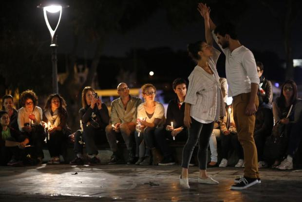 Dancers of the Zfin Malta Dance Ensemble, Malta's national dance company, perform short live-art works in commemoration of migrants' lives lost at sea as people holding candles watch, in St Anne's Square in Sliema on April 29. Photo: Darrin Zammit Lupi