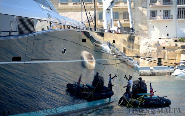 Crewmembers wash the side of a luxury yacht in Grand Harbour Marina, Birgu on May 23. Photo: Matthew Mirabelli