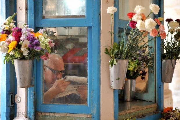 A Valletta florist reads a newspaper on April 20. Photo: Chris Sant Fournier