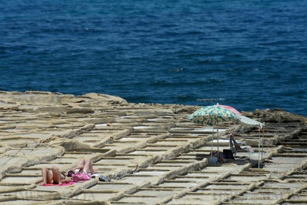 Sunbathers soak up the sun in Baħar iċ-Ċagħaq on July 19. Photo: Matthew Mirabelli