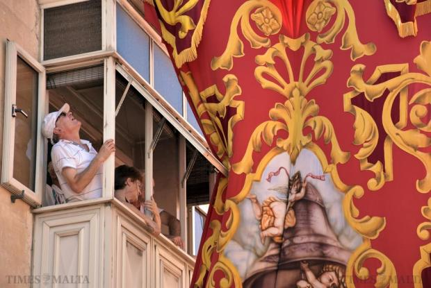 A man looks out of his balcony to arrange a street decorative banner during the feast of St Helen's in Birkirkara on August 22. Photo: Mark Zammit Cordina