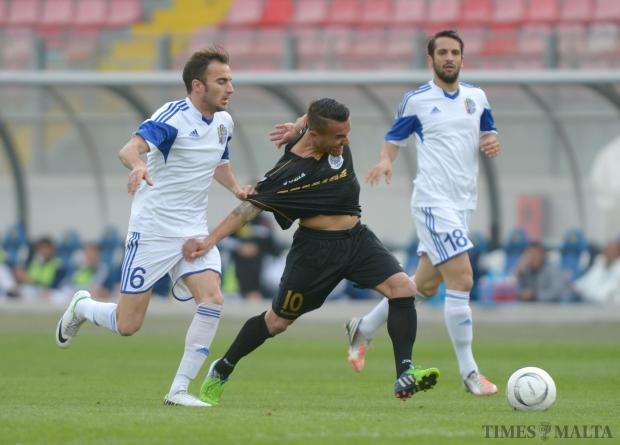 Hibernian's Andrew Cohen (centre) is held back by Mosta's Ryan Grech during their Premiership match at the National Stadium in Ta'Qali on April 4. Photo: Matthew Mirabelli