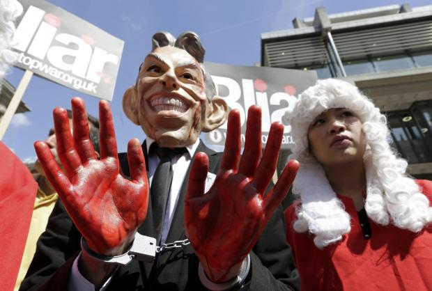 A demonstrator wearing a mask to impersonate Tony Blair protests before the release of the John Chilcot report into the Iraq war.