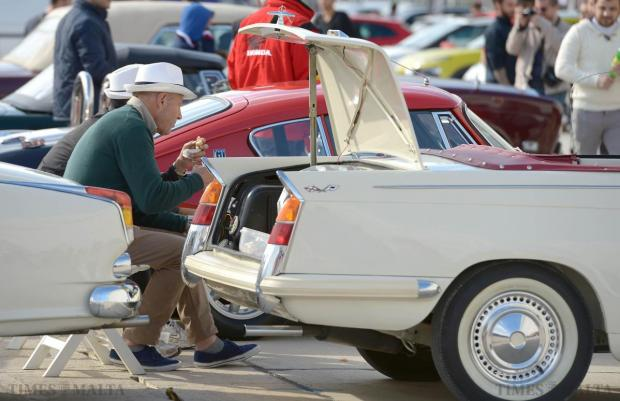 Two gentlemen stop for a bite to eat during the Paqpaqli Ghall-Istrina car show at Hal Farrug on December 7. Photo: Matthew Mirabelli